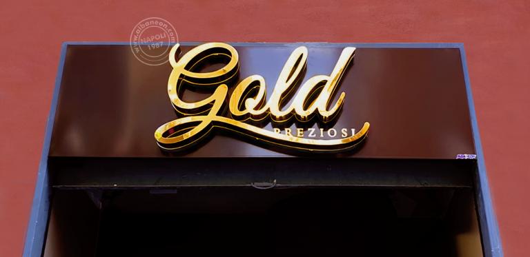 Lettere scatolate in acciaio con finitura colore oro lucido. L'illuminazione a led, a luce riflessa, genera un elegante effetto outline sul fondo della tabella che è realizzato con un box in alluminio traforato marrone