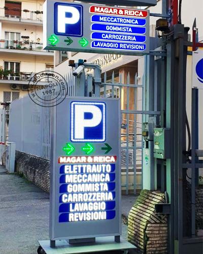 Insegne luminose a led per parcheggio a Napoli. Box a bandiera bifacciale con grafiche in rilievo in plex, P e frecce luminose a led. Totem a batteria con diciture luminose, P parcheggio e frecce animate con led a vista.